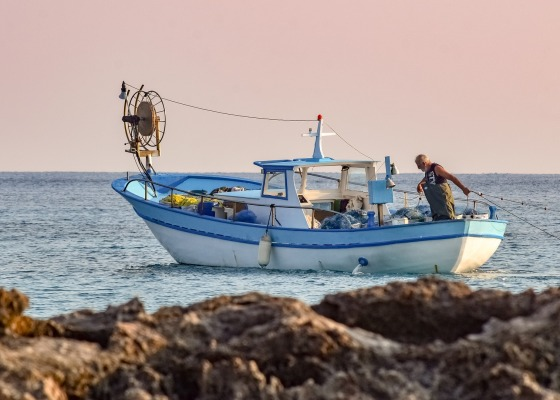 A fisherman is working alone at the ocean in the sunset. The boat is small - blue and white.