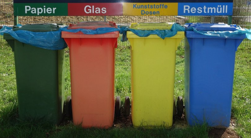 Four Colorful recycling bins for paper, glass, plastic jars, and mixed waste. Clear instructions and well-planned solutions would make recycling more appealing for citizens.
