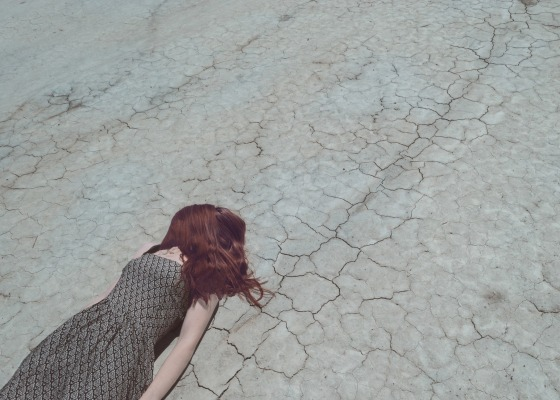 A red-haired woman is lying down on the ground in the desert. Efforts towards sustainability can sometimes feel overwhelming, and all the bad news can create eco-anxiety.