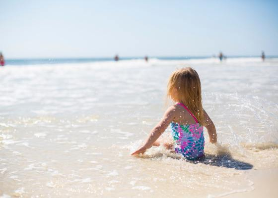 A young blond child is sitting in the shallow beach in the water. The sun is shining and she enjoys the water. Sunprotection is essential but not all the products are safe to us nor the nature.