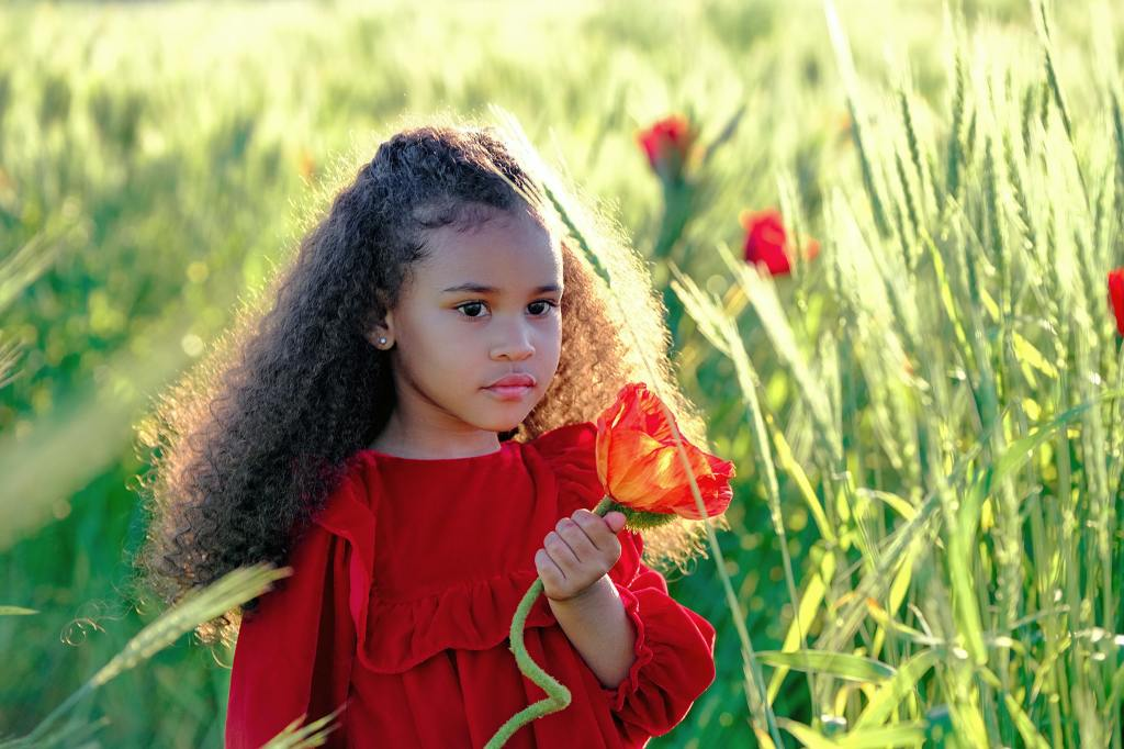 A girl with a flower. A 6-year-old girl is walking on the field; it's later afternoon hours. She is holding a red flower in her hand - the same color as her dress is. She has dark brown curly hair and deep brown beautiful eyes. The sun is shining, making the hay look like green gold. Let's save our planet for future generations.